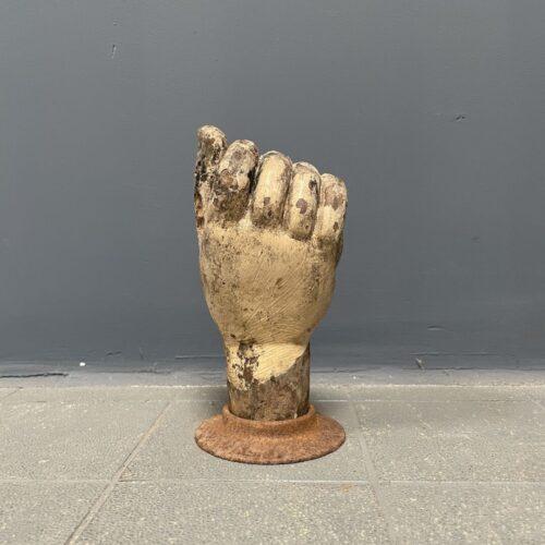 Verweerde houten hand op gietijzeren voet