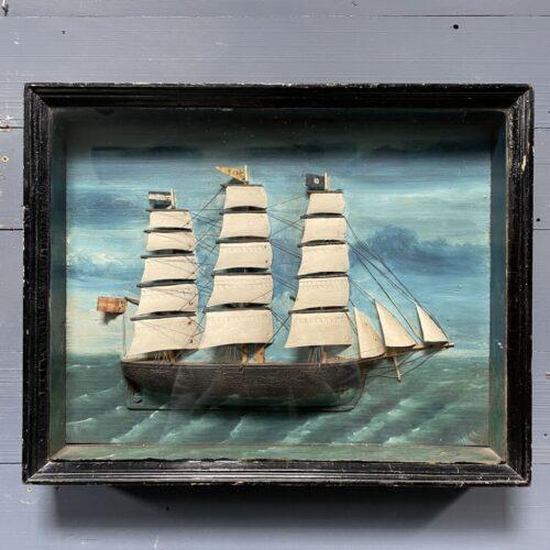 Ingelijst volkskunst schip achter glas
